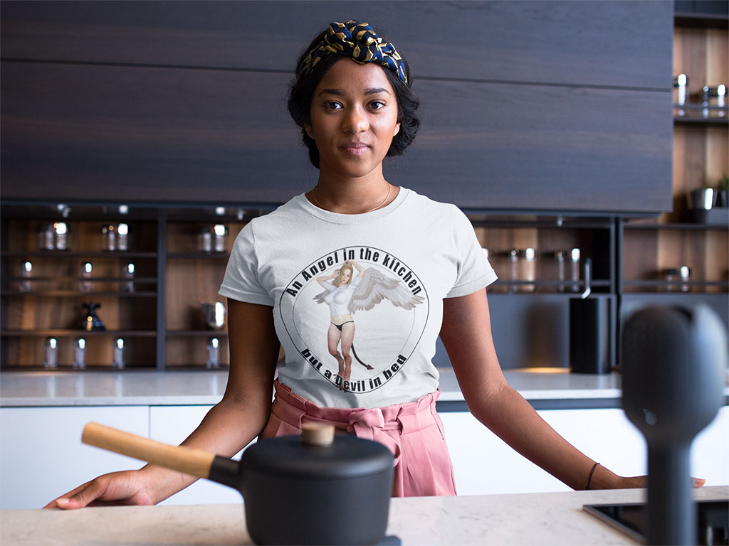 """A woman cooking when wearing a t-shirt with the text """"An angel in the kitchen but a devil in bed""""."""